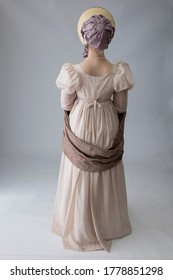 A Regency woman in a pink dress against a plain studio backdrop