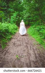 Regency woman wearing coat walking along a woodland path