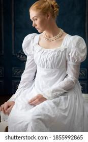 A Regency woman in a white muslin dress alone in a room