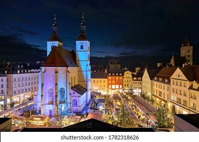 Regensburg, Germany. High angle view of the city's main Christmas market on the Neupfarrplatz (New Parish Square) around the Neupfarrkirche (New Parish Church) in dusk.