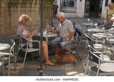 REGENSBURG, GERMANY - SEP 9, 2016 - Couple with their dachshund at an outdoor coffee shop in  Regensburg, Germany