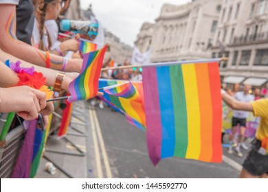 Regent Street, LONDON, UK - 6th July 2019 - Around 1.5 million people descend onto the streets of London to attend Pride In London 2019. Supporters waving LGBT Flag behind barriers