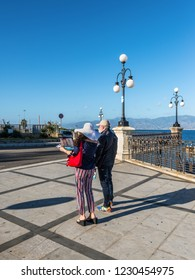 Reggio Calabria, Italy - October 30, 2017: Couple of travelers using map for sightseeing at waterfront promenade Lungomare Falcomata in Reggio Calabria, Southern Italy.