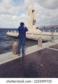 Reggio Calabria, Italy/Italy - December 2018 : Man while photographing the  Sculpture at Athena Promachos of the Bonfiglio sculptor, near Sea of Reggio Calabria