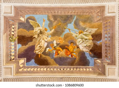 REGGIO EMILIA, ITALY - APRIL 13, 2018: The ceiling fresco of angels with the trumphs in church Chiesa di San Pietro by Anselmo Govi (1939).