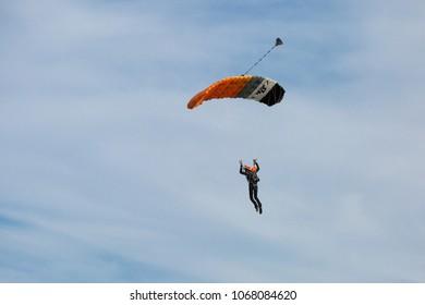 Reggio Emilia, Italy - May 2017: Parachutist with Orange Parachute against Blue Sky preparing for Landing