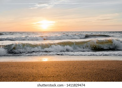 Regime time for the photographer. Beautiful waves, the sky and the gold coast at sunset. Sunset over the Baltic Sea.