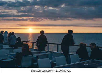 Region Sjælland, Denmark - July 22, 2016: Ferry sailing across the Baltic Sea, crowd silhouette watching the sunrise on the sea