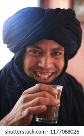 """Drâa-Tafilalet region / Morocco - 11/05/2016 :  Portrait of a young Berber man wearing a blue Moroccan shesh or Tuareg turban, smiling and drinking hot mint tea (called the """"berber whisky""""), Morocco"""