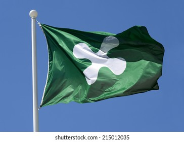 Regional flag of Lombardy, Italy flying in the breeze from the top of a flagpole against a sunny blue sky