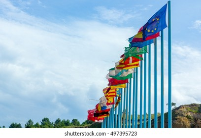 Regional flags of Spain in the wind over long blue poles