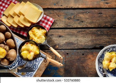 Regional Swiss cuisine with raclette cheese melted over fresh boiled potatoes in an overhead side border view with ingredients and prepared servings on rustic wood with copy space