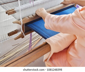 A regional weaver sit weaving blue Thai silk cloth in pattern by using her hand and local weaving machine