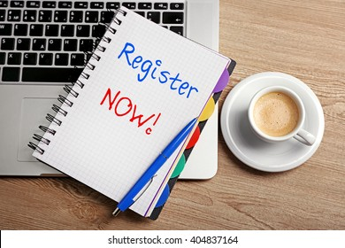 Register now written in notebook, laptop and cup of coffee on table, top view