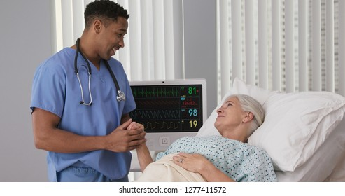 Registered nurse holding hand of ill female woman in hospice