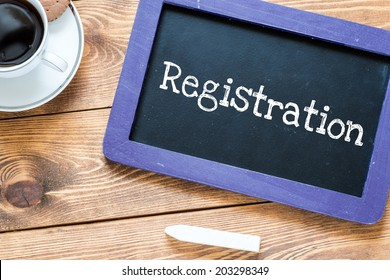 Registration handwritten with white chalk on a blackboard, cup of coffee and biscuit on a wooden background