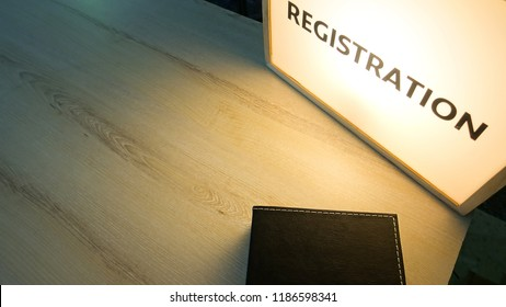 The registration lightbox and Black Leather Book on wooden table for event with copy space.
