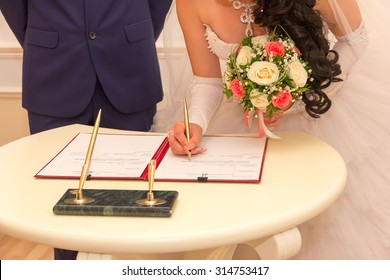 registration of marriage, the bride with a bouquet of flowers signed a marriage contract with a ballpoint pen, selective focus