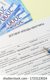 "Registration and signing of the housing rent agreement. Russian text ""the lease of the apartment,"" ruble bills for payment and handle"