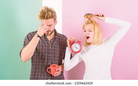 Regret late regime. Couple morning awakening alarm clock. Create healthy rest regime to sleep enough. We should go to bed earlier. Woman and man sleepy tousled hair drink morning coffee.