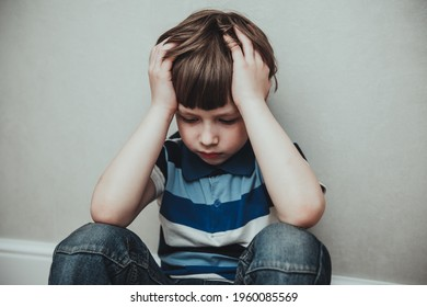 Regret sad little boy sitting alone loneliness,stressed depressed child crying having depression, anxiety, trouble of mental health, lonely kid boy with hands on head, Hikikomori Syndrome Disease