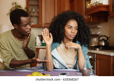 Regretful guilty young Afro-American man in glasses offering hand to his angry girlfriend as a sign of reconciliation after serious quarrel but woman seems refusing all apologies and excuses