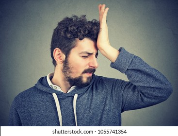 Regrets wrong doing. Portrait silly young man, slapping hand on head having a duh moment isolated on gray background. Negative emotion expression feeling, body language, reaction
