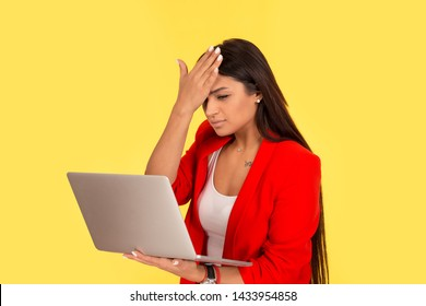 Regrets wrong doing while working online. Sad woman, slapping hand on head having duh moment while looking holding laptop computer isolated on yellow background. Negative emotion feeling body language