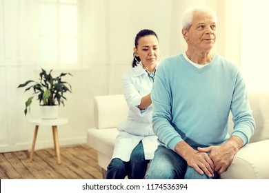 Regular checkup. Selective focus on a pensive elderly man sitting on a sofa while a mature medical worker listening to his lungs.