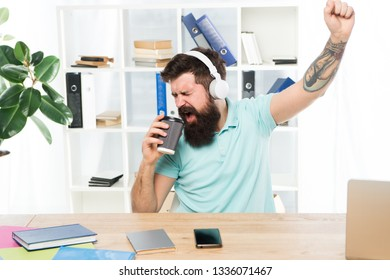 Regular office day. Man bearded guy headphones sit office listen music sing song. Worker with coffee cup begin working day with favorite song. Inspired and full of energy. Office life rhythm.