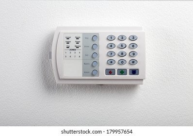 A regular security systems keypad with buttons and a plastic flap mounted on a white textured wall