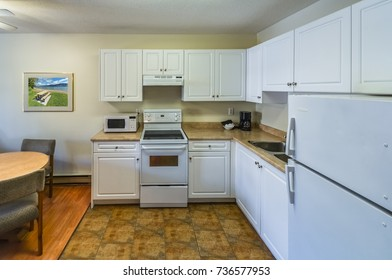 Regular white kitchen with the table and chairs in dinner area