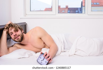 Regulate your bodys clock. Man unshaven tousled hair wakeful face having rest. Good morning. Man unshaven lay bed hold alarm clock. Stick schedule same bedtime wake up time. Enough sleep for him.