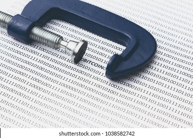 "The regulation of bitcoin concept image consisting of a clamp, binary code and the word, ""BITCOIN"""