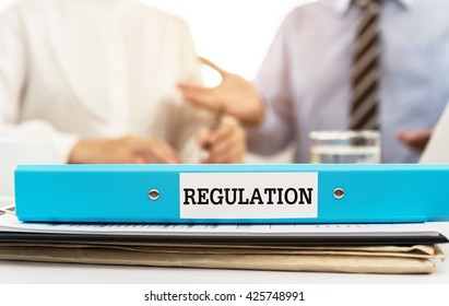 Regulation documents file on desk in meeting room. Rules, Regulations Business Concept.