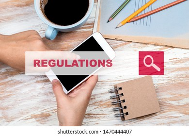 Regulations Concept. Hands holding phone on a wooden table