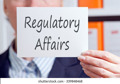 Regulatory Affairs - Businesswoman holding sign with text in the office