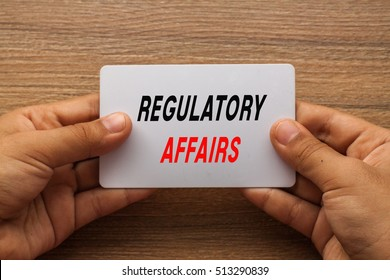 Regulatory Affairs written on white card holding with two hands