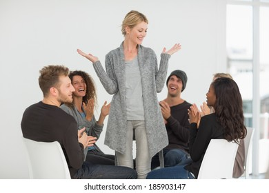 Rehab group applauding happy woman standing up at therapy session