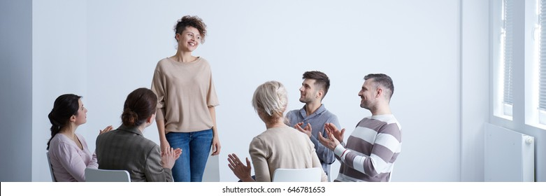 Rehab group applauding happy woman standing up during session