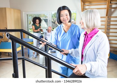 Rehab physical exercises for elderly people, aged senior couple at the gym assisted by multi ethnic nurses.