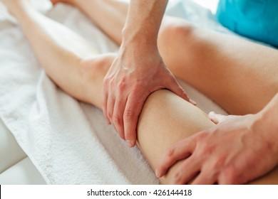 Rehabilitant is massaging his patient leg