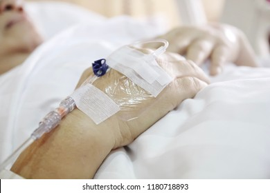 Rehabilitation after surgery. The doctor will give old lady an IV (Intravenous) / a saline drip (saline solution), patient sleep in the bed with white blanket - close up hand