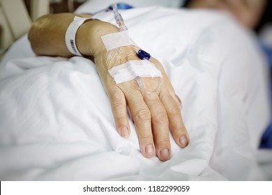 Rehabilitation after surgery. The doctor will give old lady an IV (Intravenous) / a saline drip (saline solution), patient sleep in the bed with white blanket - Focus on hand