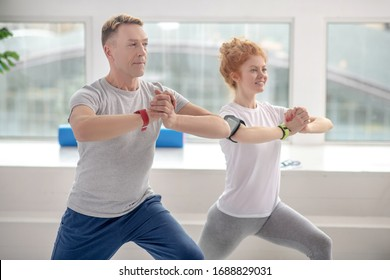 At rehabilitation center. Female patient and male physiotherapist lunging together, smiling