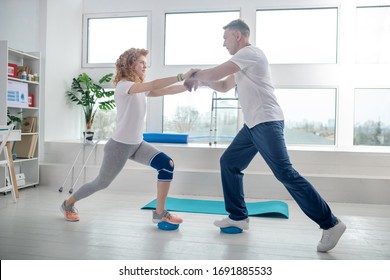 At rehabilitation center. Male physiotherapist and female patient lunging together