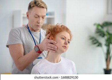 At rehabilitation center. Male physiotherapist holding head of female patient