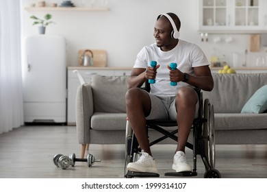 Rehabilitation disabled people at home, pandemic, covid-19 infection. Smiling adult black man in wheelchair in wireless headphones do exercises with dumbbells in room interior, looks at empty space