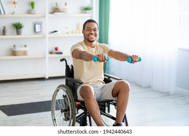 Rehabilitation of disabled people. Young African American man in wheelchair working out at home