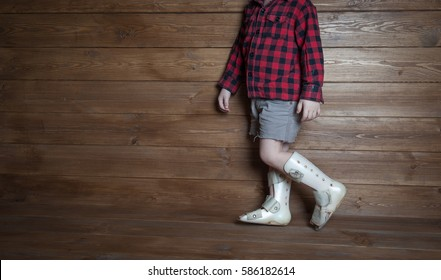 Rehabilitation at home - cute kid boy in orthoses is going to have physical musculoskeletal therapy. Valgus deformity of legs. orthotics measurment.